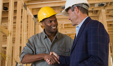 construction worker shaking hands with architect