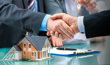 shaking hands over a contract and a small model home
